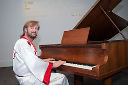 """© Licensed to London News Pictures. 27/08/2015. London, UK. Benny from ABBA tribute band, Björn Again, performs at the photocall at Sotheby's for the upcoming auction of the """"ABBA piano"""", the instrument on which ABBA recorded their most celebrated songs including """"Mamma Mia"""", """"Waterloo"""" and """"Dancing Queen"""".  Estimated at £600,000-800,000, the piano will be part of Sotheby's Rock and Pop auction on 29 September. Photo credit : Stephen Chung/LNP"""