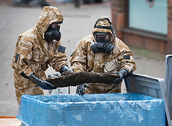 © Licensed to London News Pictures. 24/04/2018. Salisbury, UK. Members of the armed forces remove an item from contaminated soil in the area at the Maltings where a bench was earlier removed as the cleanup operation begins in Salisbury. Former Russian Spy Sergei Skripal and his daughter Yulia were poisoned using a nerve agent in the city last month. Experts have warned that 'Toxic levels' of the nerve agent novichok could still be present at hot spots around the city. Photo credit: Peter Macdiarmid/LNP