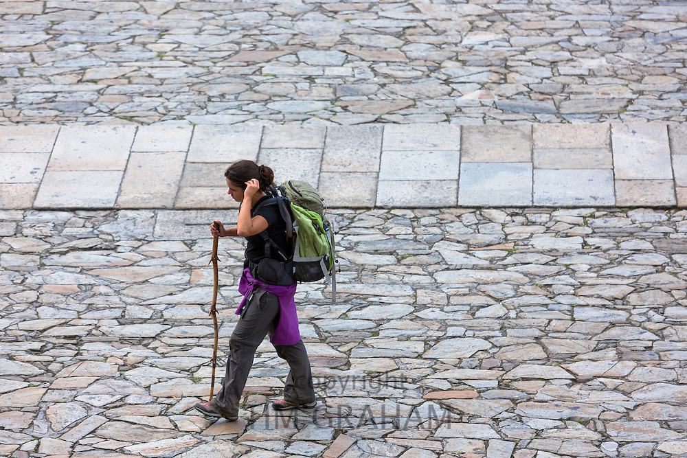 Pilgrim with walking pole ends her pilgrimage in Cathedral square of Santiago de Compostela, Galicia, Spain