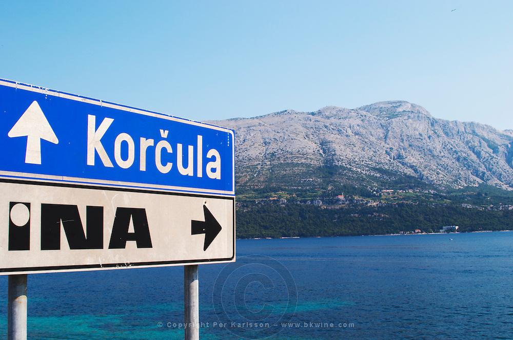 Road sign saying Korcula, view across the sea towards the Peljesac peninsula and the Sveti Ilija mountain. Korcula Island. Korcula Island. Dalmatian Coast, Croatia, Europe.