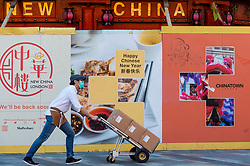 © Licensed to London News Pictures. 05/02/2021. LONDON, UK. A worker wearing a facemask walks past construction hoarding in Chinatown ahead of the Chinese New Year festival, the Year of the Ox.   The normal parade and festivities have been cancelled this year due to the ongoing coronavirus pandemic and the organisers will instead host celebrations online.  Photo credit: Stephen Chung/LNP