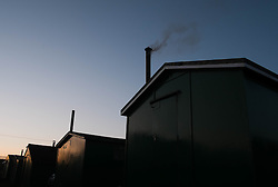 © Licensed to London News Pictures. <br /> 08/03/2015. <br /> <br /> South Gare, Redcar, United Kingdom<br /> <br /> A chimney on one of the fisherman's huts at South Gare near Redcar smokes away at dusk.<br /> <br /> Photo credit : Ian Forsyth/LNP