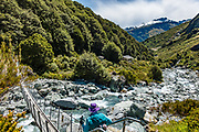 After 8 hours of tramping over Rees Saddle from the previous hut, we cross the swing bridge over Snowy Creek to Dart Hut on the Rees-Dart Track. Mt. Lydia rises above in Mount Aspiring National Park, Otago region, South Island of New Zealand.