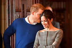 1 in series of 10. File photo dated 18/1/2018 of Prince Harry whispering to Meghan Markle as they watch a performance by a Welsh choir in the banqueting hall during a visit to Cardiff Castle.