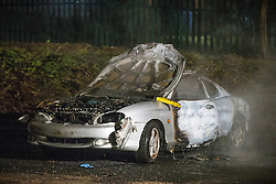 © Licensed to London News Pictures . 05/11/2015 . Oldham , UK . A burned out car on West End Street . Manchester Fire reports receiving more than 300 calls in less than 7 hours, from 4.30pm, including to buildings, cars and wheelie bins set alight by arsonists . At some calls fire crews were subject to vandalism , including a hose being sliced whilst it was being used to fight a fire in Leigh and bricks being thrown at crews attending a job in Miles Platting . Fire crews deal with arson attacks across Greater Manchester during Bonfire Night . Photo credit : Joel Goodman/LNP