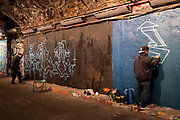 Graffiti artists at work at the popular Leake Street Arches on 13th April 2021 in London, England, United Kingdom. Leake Street is a road tunnel in Lambeth, where graffiti is tolerated and encouraged regardless of the fact that it is against the law. The street is about 300 metres long, runs off York Road and under the platforms and tracks of Waterloo station.