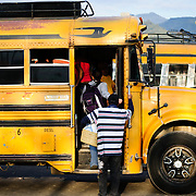 Passengers board a chicken bus in Antigua Guatemala. Famous for its well-preserved Spanish baroque architecture as well as a number of ruins from earthquakes, Antigua Guatemala is a UNESCO World Heritage Site and former capital of Guatemala.