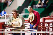 "01 SEPTEMBER 2011 - ST. PAUL, MN: Chute workers bow their head in prayer before the high school rodeo at the Minnesota State Fair. The Minnesota State Fair is one of the largest state fairs in the United States. It's called ""the Great Minnesota Get Together"" and includes numerous agricultural exhibits, a vast midway with rides and games, horse shows and rodeos. Nearly two million people a year visit the fair, which is located in St. Paul.   PHOTO BY JACK KURTZ"
