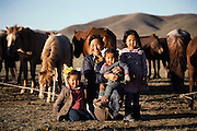 Rural life 35km from Ulaanbaatar, Mongolia. The mother in a herding family pauses from her chores to be photographed with three of her 5 children. The live in a traditional ger (round tent built from canvas, strong poles, and wool felt). Material World Project.