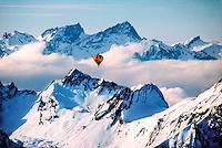 Hot air balloon rises through the fog in the Swiss Alps, during the International Hot Air Balloon Week, near Chateau d'Oex, Switzerland
