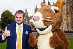 """Nature campaigners accompanied by a  giant red squirrel, Bob, urge MPs to """"Vote For Bob"""" during a photocall outside Parliament. Their aim is to get MPs to support nature in Britain. Pictured: Andrew Stephenson MP poses with Bob the red squirrel."""