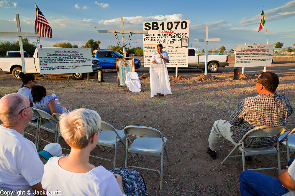 11 JULY 2010 - PHOENIX, AZ: About 40 people gather nightly at an intersection in an immigrants' neighborhood in Phoenix to pray the rosary in opposition to Arizona SB 1070, a law that requires local police to question the immigration status of people they have probably cause to believe might be in the US illegally. Probable cause can include a traffic stop like speeding or having a cracked windshield. The law is being challenged in federal courts by several parties, including the US Department of Justice, which claims the law is unconstitutional because only the federal government can enact and enforce immigration laws.      PHOTO BY JACK KURTZ