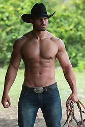 shirtless sweaty cowboy with a muscular body outdoors on a ranch