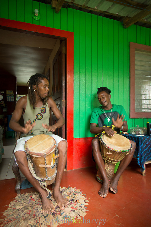 Two young male local musicians playing the drums outside a house, Little Corn Island, Nicaragua