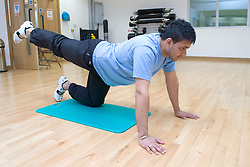 Young man doing floor exercising in an aerobics class at his sports leisure centre,