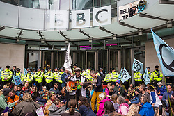London, UK. 11 October, 2019. Climate activists from Extinction Rebellion, including two standing on the glass parapet, block the main entrance to the BBC's New Broadcasting House on the fifth day of International Rebellion protests. They were demanding that the broadcaster 'tell the truth' regarding the climate emergency.