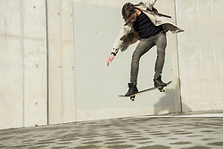 Young man jumping with skateboard in mid-air, Munich, Bavaria, Germany