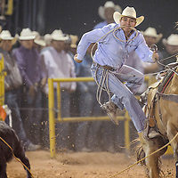 Tie-down roper Kyle Dennison leaps from his horse for an 11.8-second run during the Navajo Nation Fair Rodeo Friday in Window Rock.