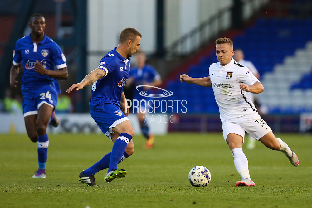 Sam Hoskins of Northampton Town runs at Peter Clarke of Oldham Athletic during the EFL Sky Bet League 1 match between Oldham Athletic and Northampton Town at Boundary Park, Oldham, England on 16 August 2016. Photo by Simon Brady.