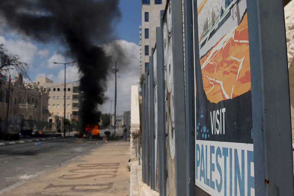 Bethlehem, Palestine. 15 May 2018. A 'Visit Palestine' poster is seen in front of a burning barricade during protests on the 70th anniversary of the Nakba (Catastrophe) when over 700,000 Palestinians were forcibly moved from their homes during the creation of Israel. © Craig Redmond