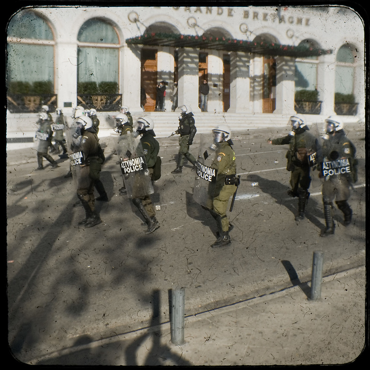 Riot police chasing protestors in  King George street in Syntagma Athens. <br /> <br /> Following the murder of a 15 year old boy, Alexandros Grigoropoulos, by a policeman on 6 December 2008 widespread riots, protests and unrest followed lasting for several weeks and spreading beyond the capital and even overseas<br /> <br /> When I walked in the streets of my town the day after the riots I instantly forgot the image I had about Athens, that of a bustling, peaceful, energetic metropolis and in my mind came the old photographs from WWII, the civil war and the students uprising against the dictatorship. <br /> <br /> Thus I decided not to turn my digital camera straight to the destroyed buildings but to photograph through an old camera that worked as a filter, a barrier between me and the city.