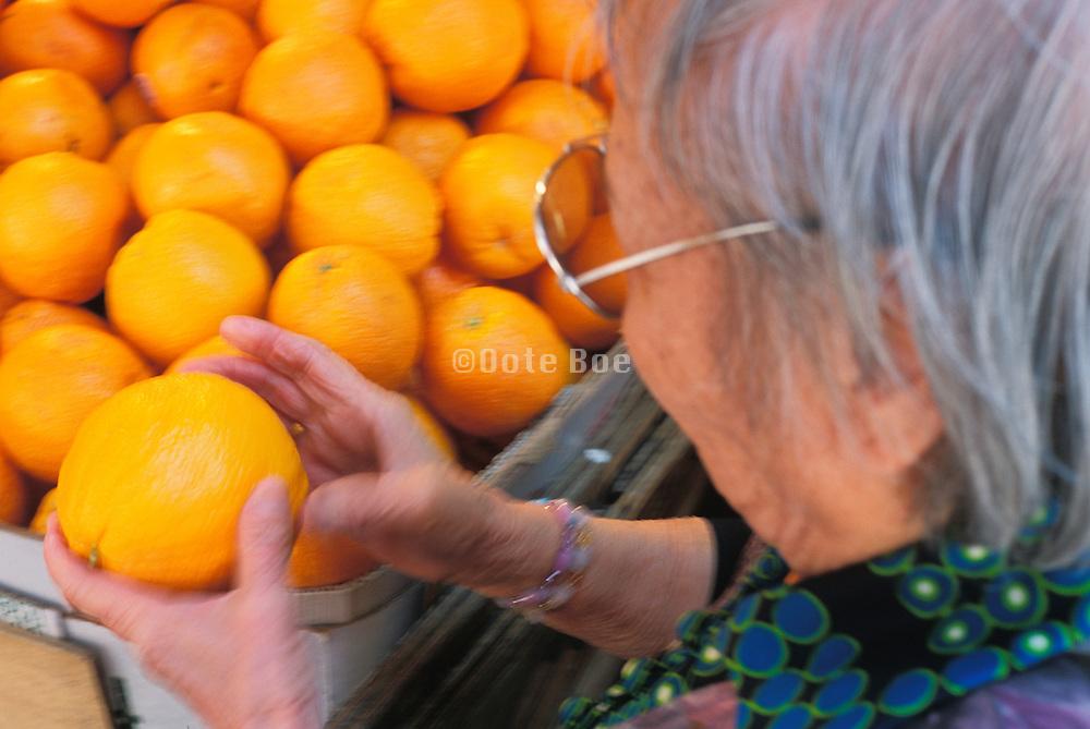 Elderly Asian woman checking an orange