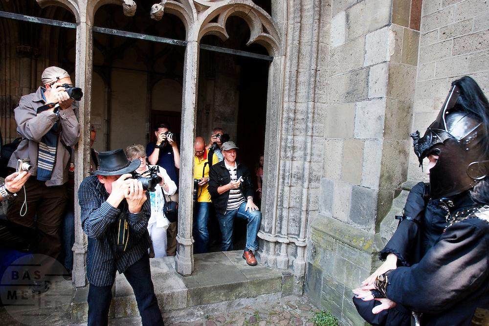 Fotografen verdringen zich rondom goths. In Utrecht komen goths uit heel Europa bij elkaar voor het jaarlijkse festival Summer Darkness. Tijdens het driedaags festijn zijn er onder andere optredens van bands, een markt en een modeshow. Het is ook een kwestie van zien en gezien worden.<br /> <br /> Photographers are crowding around a group of goths at Summer Darkness. During the festival goths from all over Europe are coming to Utrecht to meet and enjoy music, a market, a fashion show and more.