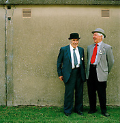 Tom Alty, right, commentator and judge of Bartle, Lancashire, with Stan Samuels, 'Showing pigs is a performance because you don't have a halter and rope or bridle, you just have a bat [a stick] and a board. You have to have an empathy between pig and handler, but even the good pigs are not as obedient as you'd like. At one show about 15 years ago I asked my wife, who had never taken an animal in the ring, to walk round an old Large Black sow. It was a placid pig, but suddenly there was a grunt and a rush, and the pig disappeared into the horticultural tent, which housed, among other things, a display of eggs. My wife has never been to a show since. The Great Yorkshire Show, one of Britain's biggest agricultural shows, is famous for its competitive displays of livestock. The event, established in 1837, attracts over 125 000 visitors a year and has over 10 000 entries to its pedigree competitions ranging from pigeons and rabbits to bulls and shire horses.