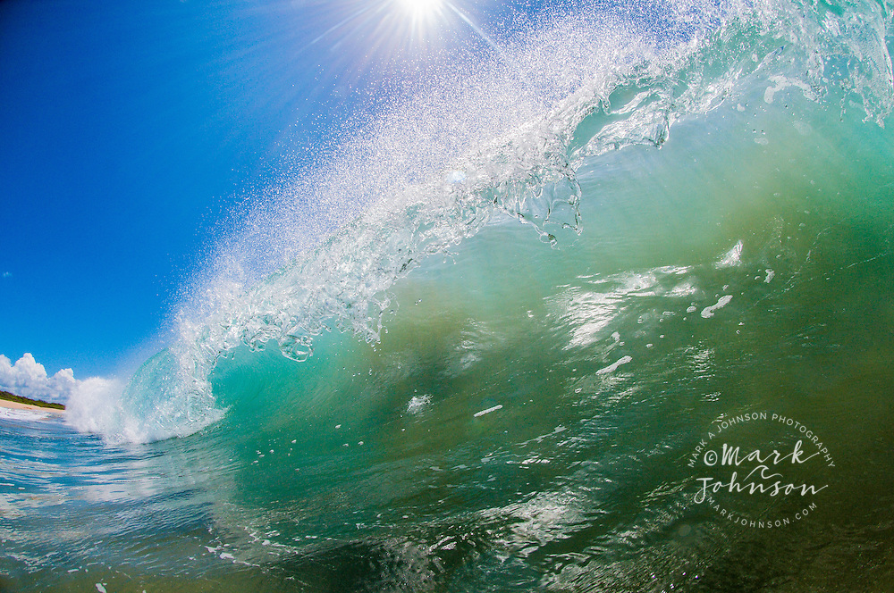 Backlit breaking wave with beautiful falling water drops from the lip, Hawaii