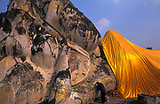 THAILAND: Ayuthaya.A pilgrim wais the Sleeping (reclining) buddha at Ayuthaya, during the scared season of the Buddhist New Year, when the buddha is adorned in golden robes.