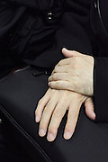 hands of a businessman resting on top of his soft black briefcase