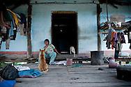 A strange woman sits and faces a dog. Messy deck of a Reungao ethnic tribe house. Kontum plateau, Pleiku area, Vietnam, Asia
