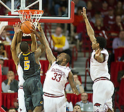 Feb 16, 2013; Fayetteville, AR, USA; Missouri Tigers guard Keion Bell (5) takes a shot on Arkansas Razorbacks forwards Marshawn Powell (33) and Coty Clarke (4) during a game against the Missouri Tigers at Bud Walton Arena. Arkansas defeated Missouri 73-71. Mandatory Credit: Beth Hall-USA TODAY Sports