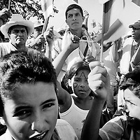 Adults and children wave flags; white for peace and the national colours during a peace march at a FARC camp in Los Posos, Caqueta.<br />