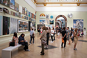 People looking at the artworks in one of the main galleries at the Royal Academy for the Summer Show in London, United Kingdom. The Summer Exhibition is an open art exhibition held annually by the Royal Academy in Burlington House, Piccadilly in central London, England, during the months of June, July, and August. The exhibition includes paintings, prints, drawings, sculpture, architectural designs and models, and is the largest and most popular open exhibition in the UK. It is also the longest continuously staged exibition of contemporary art in the world.