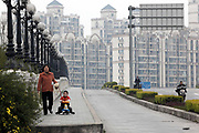 A woman and a child walk in front of a roll of new apartment buildings in Shanghai, China on 07 April, 2009.  By making short-term and sometimes hasty bets on China's property market, analysts say, some of the world's biggest financial institutions such as Morgan Stanley, Merry Lynch, and Deutsche Bank,  may have lost as much as $10 billion.  For the past decade, Shanghai has underwent the largest reconstruction in recorded history, over 20 million square meters of land, approximately a third of Manhattan, were developed between year 200 and 2005 alone. Despite that however, housing prices have seen a rapid increase, putting the prospect of owning a decent sized home out of the reach of ordinary Chinese citizens, especially middle to low income families.