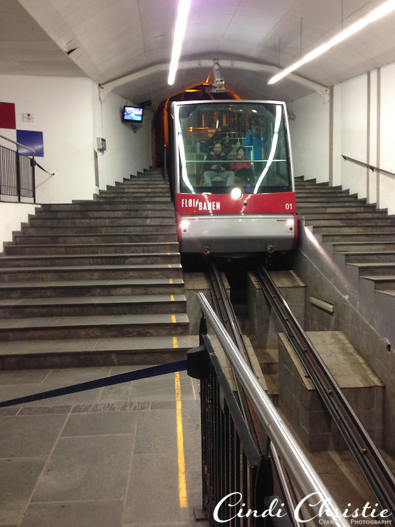 The Fløibanen funicular, which takes passengers up the steep grade to Fløyen in a matter of minutes, arrives at the station in Bergen, Norway, on May 21, 2013. The Fløytrappen observation deck, restaurant and shops can be found at the summit. People can ride down or walk the wooded pathways back to town.  (© 2013 Cindi Christie)
