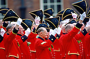 Chelsea Pensioners, dressed in their traditional uniform of bright red jacket, raising their tricorn hats and cheering during the Founder's Day Parade outside the Royal Hospital in Chelsea.