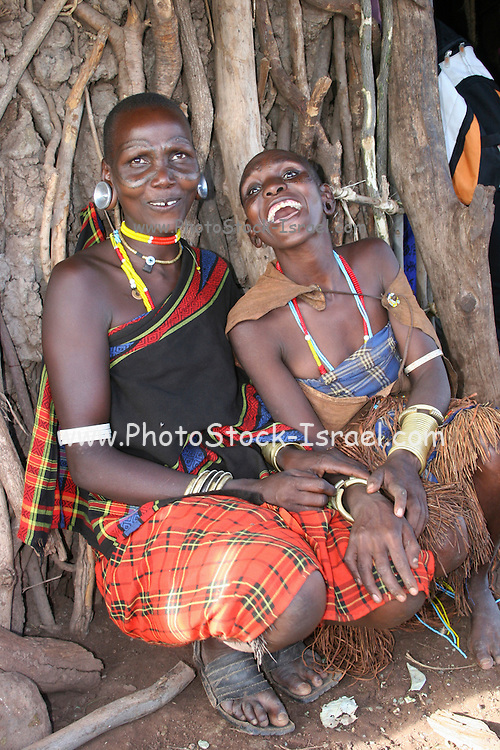 Africa, Tanzania, members of the Datoga tribe Mother and daughter with visible scarring, in traditional dress sitting in front of their wood hut smiling at camera April 2006