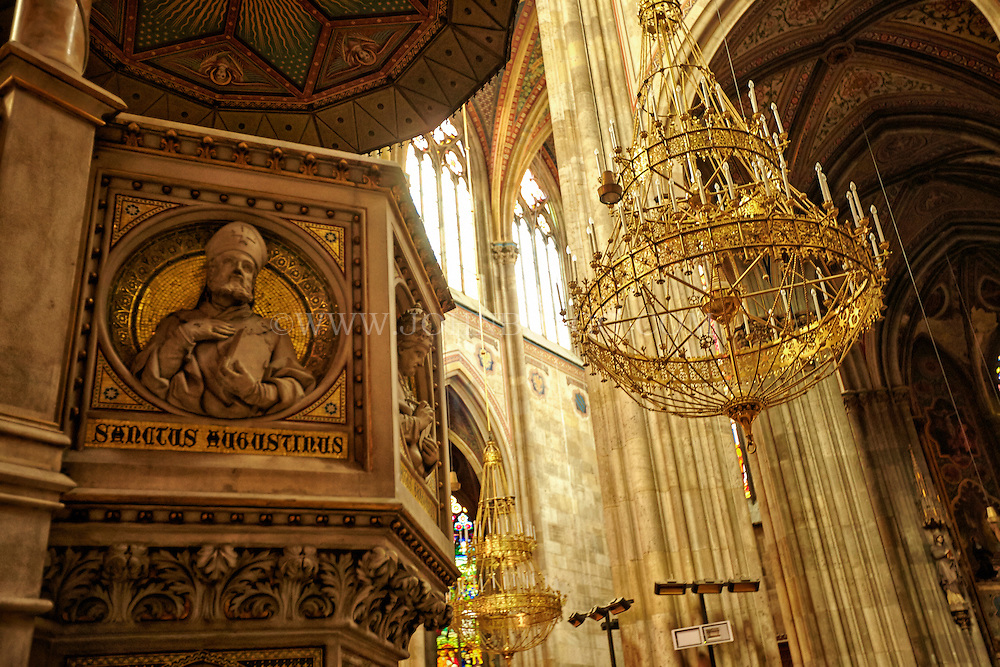 View of a Saint Augustine panel built into the pulpit (left), chandeliers, above the alter of the Votive Church, Vienna, Austria.