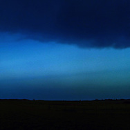 Right triptych panel of a panorama photo of a field swept by blue hues of rain as seen from afar.