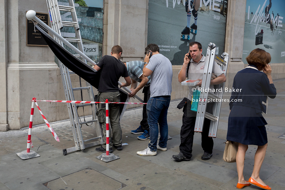 Pedestrians pass workmen preparing to erect a shop flag for sportswear retailer Asics, on 1st August 2017, in Regent Street, London, England.