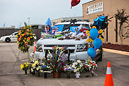 A makeshift memorial for Deputy Brad Garafola in front of the East Baton Rouge Sheriff's headquarters  covered in flowers and ballons placed on Garafola's police car in Baton Rouge on July 20, 2016.