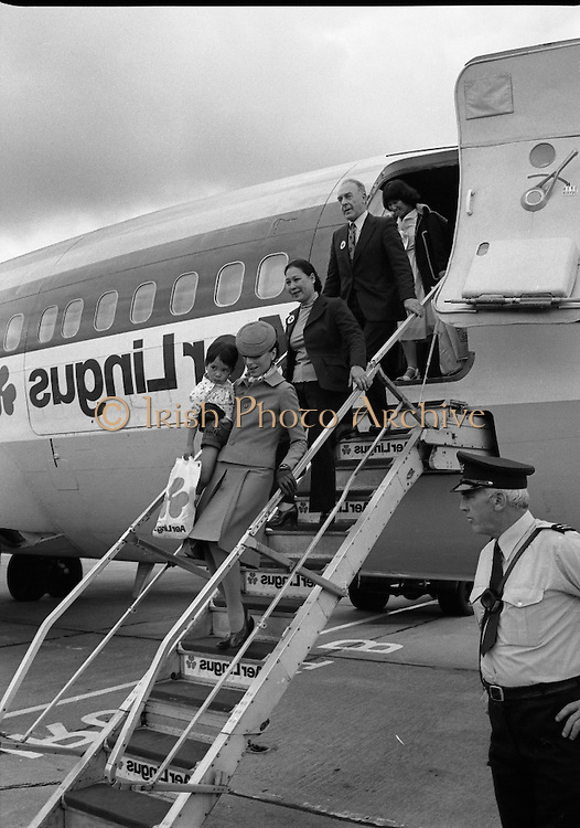 Vietnamese Refugees Arrive In Ireland.   (M85)..1979..09.08.1979..08.09.1979..9th August 1979..As part of an UNHCR initiative, Ireland agreed to take some of the Vietnamese (boat people) refugees into the country. A temporary refugee centre has been set up in the grounds of Blanchardstown Hospital to accomodate the families, from where they will be assimilated into the community..Image shows an Aer Lingus air hostess carrying a child down the stairs of the aircraft, followed by officials of the UNHCR.