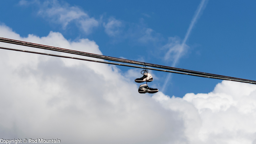 A pair of running shoes hang up high on a utility wire