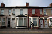 A young man cycles past a row of terraced houses in Bloomfield ward, Blackpool, Lancashire, England, United Kingdom. Bloomfield ward is the poorest council ward in Blackpool and one of the poorest in England and in 2012 had the lowest life expectancy for men in England.