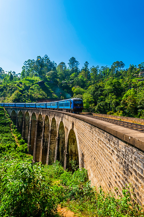 The Highland Express passes over the Nine Arch Bridge, Demodara, Ambagollapathana near Ella, Uva Province, Sri Lanka.