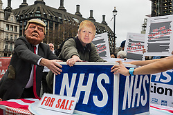London, UK. 25 November, 2019. Activists wearing Donald Trump and Boris Johnson masks fight for control of the NHS during a protest by campaigners from Keep Our NHS Public, Health Campaigns Together, We Own It and Global Justice Now in Parliament Square to call on Prime Minister Boris Johnson to end privatisation of healthcare in the National Health Service (NHS).