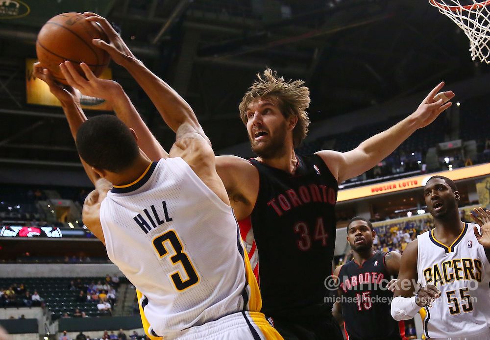 April 09, 2012; Indianapolis, IN, USA; Toronto Raptors center Aaron Gray (34) tries to strip the ball away from Indiana Pacers shooting guard George Hill (3) at Bankers Life Fieldhouse. Indiana defeated Toronto 103-98. Mandatory credit: Michael Hickey-US PRESSWIRE