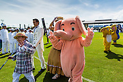 "28 AUGUST 2014 - BANGKOK, THAILAND:     A little person leads a person in an elephant suit during the parade opening the King's Cup Elephant Polo Tournament at VR Sports Club in Samut Prakan on the outskirts of Bangkok, Thailand. The tournament's primary sponsor in Anantara Resorts. This is the 13th year for the King's Cup Elephant Polo Tournament. The sport of elephant polo started in Nepal in 1982. Proceeds from the King's Cup tournament goes to help rehabilitate elephants rescued from abuse. Each team has three players and three elephants. Matches take place on a pitch (field) 80 meters by 48 meters using standard polo balls. The game is divided into two 7 minute ""chukkas"" or halves.   PHOTO BY JACK KURTZ"